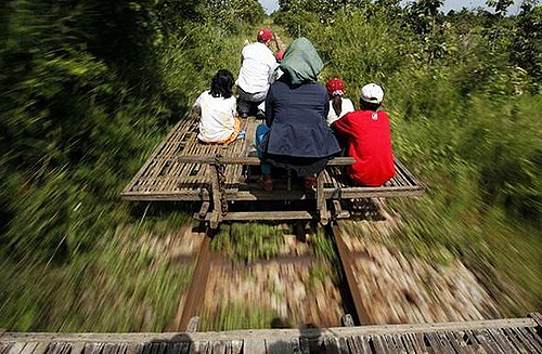 Cambodians ride a bamboo train, known locally as a lorry, at new village train station in Pusat province