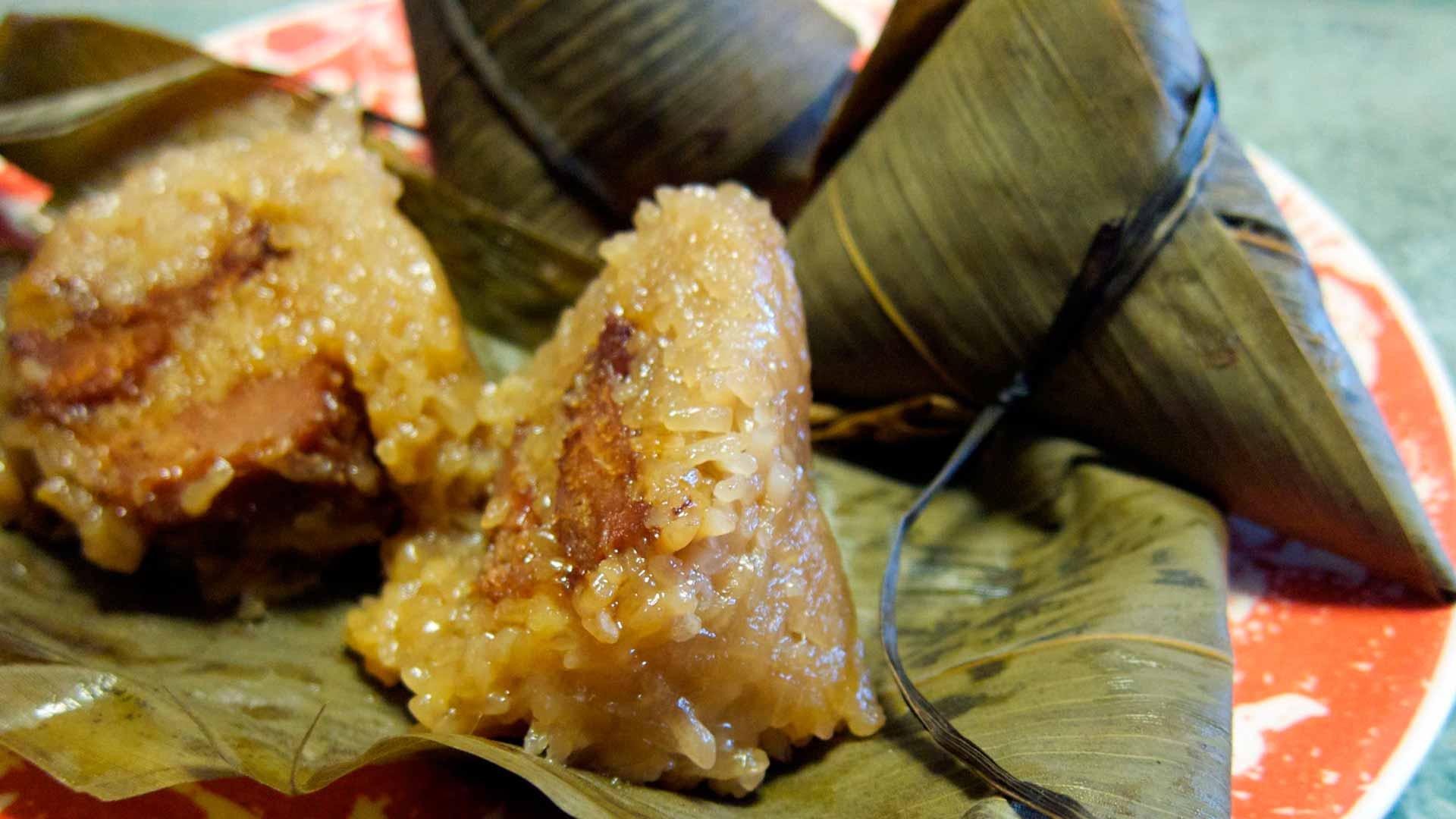 zongzi  es un popular triángulo de arroz glutinoso relleno de carne o judías dulces y enrollado con hojas de bambú